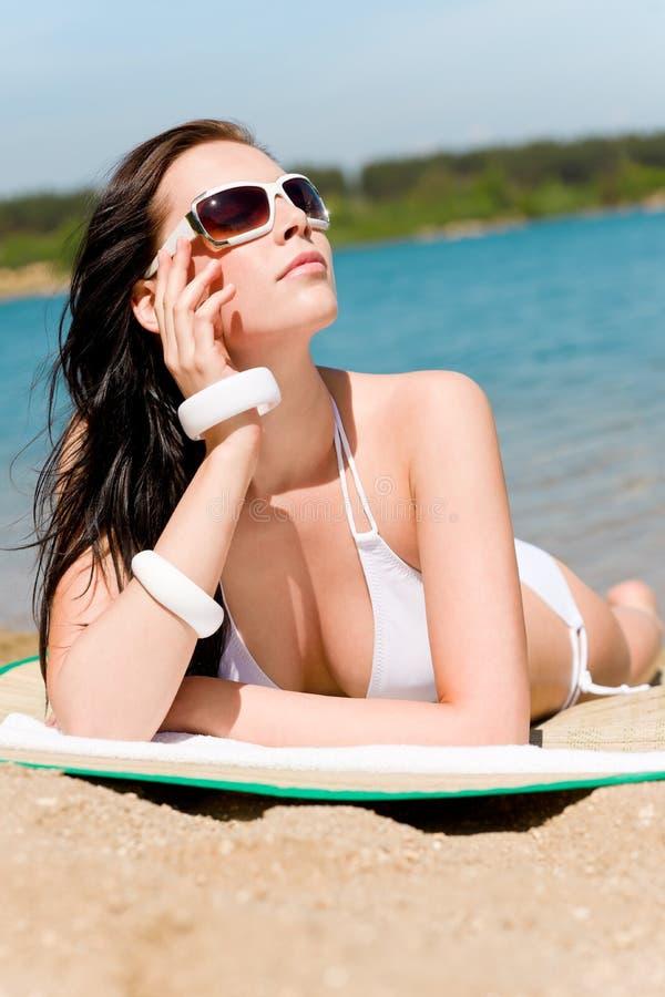 Het strand overweldigende vrouw die van de zomer in bikini zonnebaadt stock afbeelding