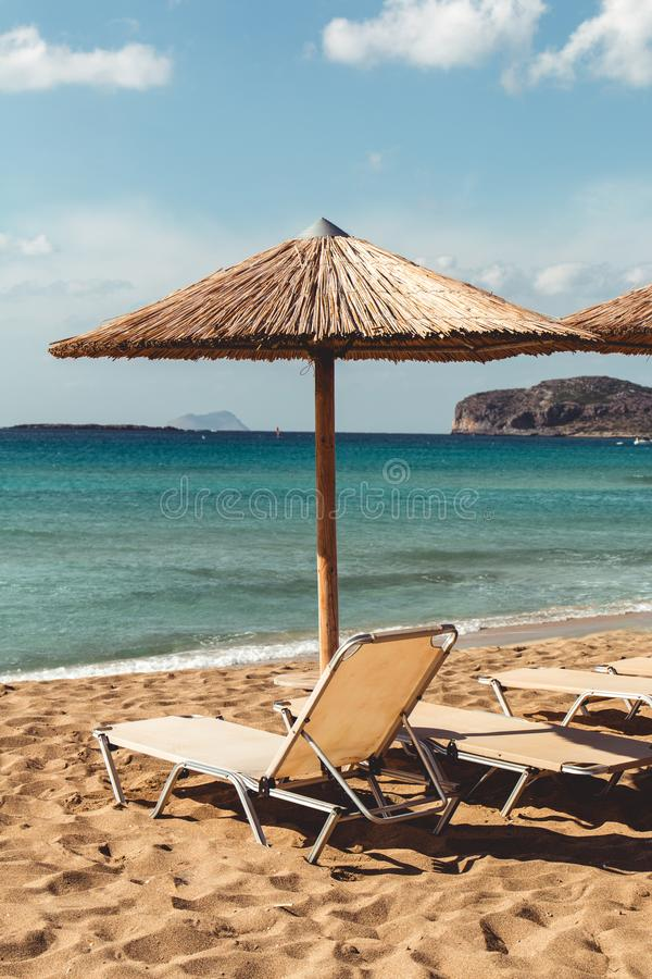 Het strand sunbed en parasol overziend turkoois water stock afbeeldingen