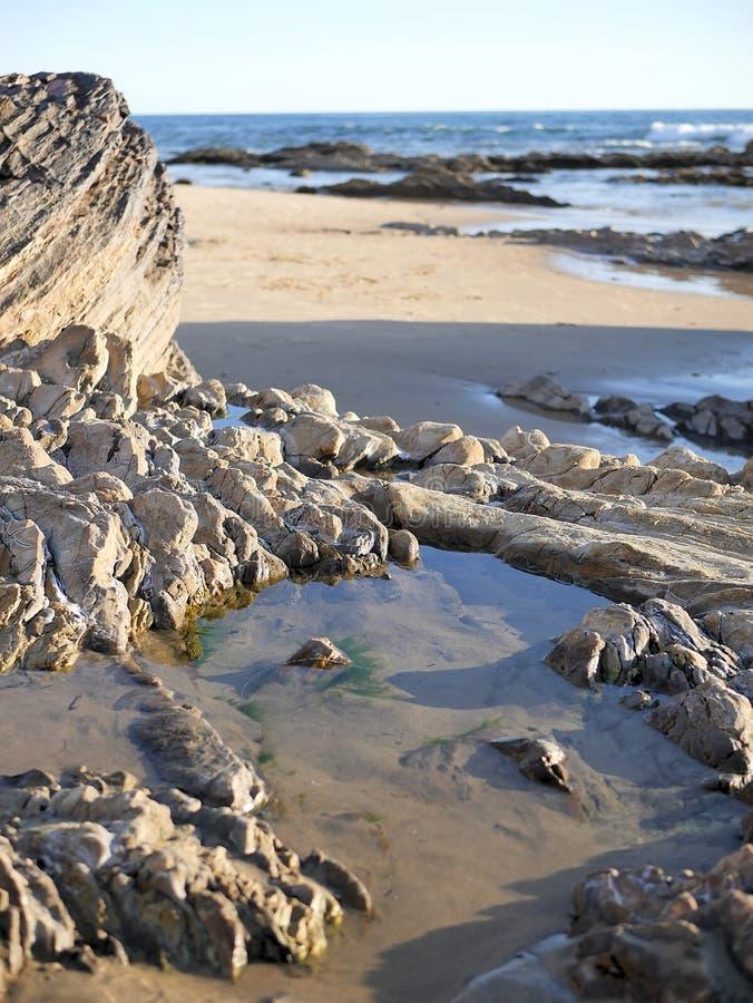 Het strand van Californië met golven, tidepools, blauwgroene water en rotsen op kust Groot voor reisbloggen, websitebanners stock foto