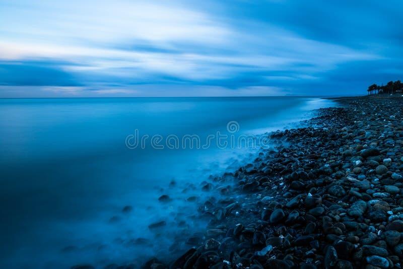Het strand van de kiezelsteen bij zonsondergang stock fotografie