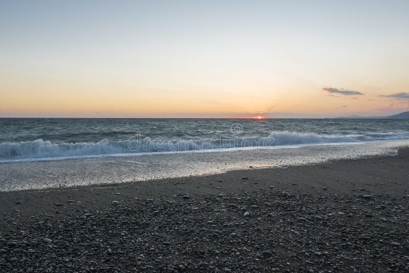 Het strand van de kiezelsteen bij zonsondergang Stormachtige overzees stock afbeelding