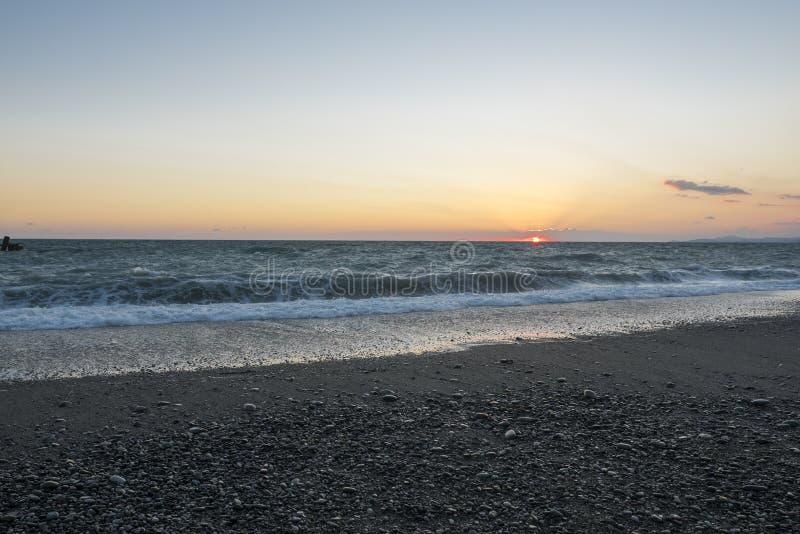 Het strand van de kiezelsteen bij zonsondergang Stormachtige overzees stock foto