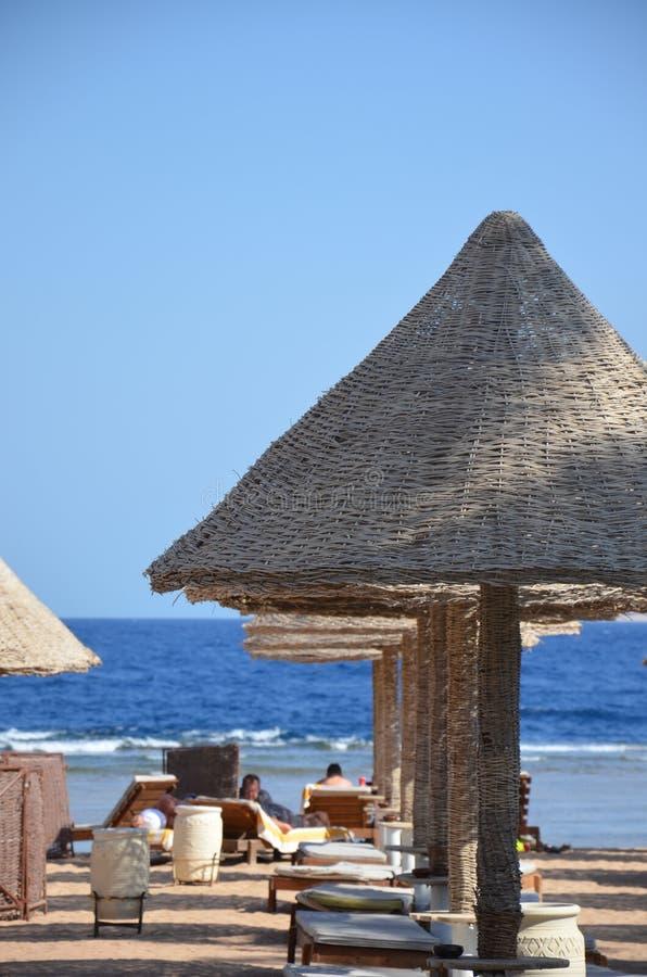 Het strand van de kiezelsteen golf nave Overzees lounger Met stro bedekt dak royalty-vrije stock foto's