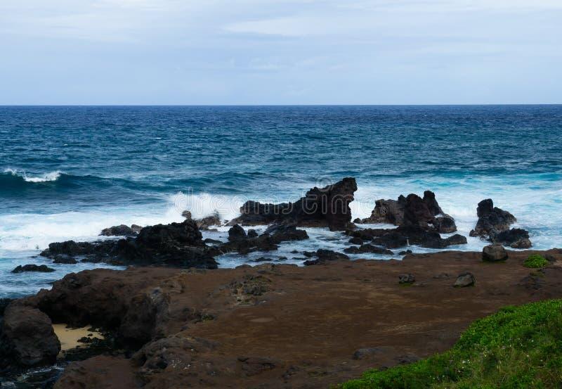 Het strand van Maui met rollende golven stock afbeeldingen