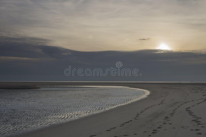 Het strand van zonsondergangmaasvlakte stock afbeelding
