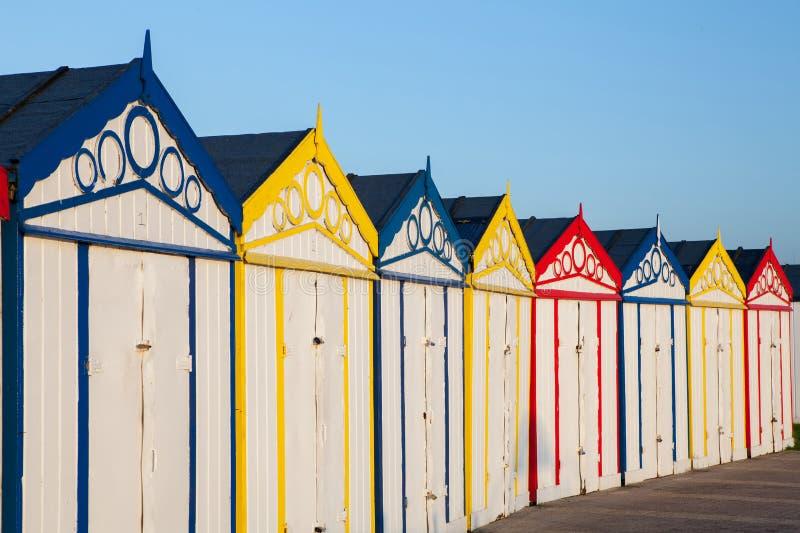 Het strandhutten van de kusttoevlucht Rij van retro helder gekleurde loodsen royalty-vrije stock afbeeldingen