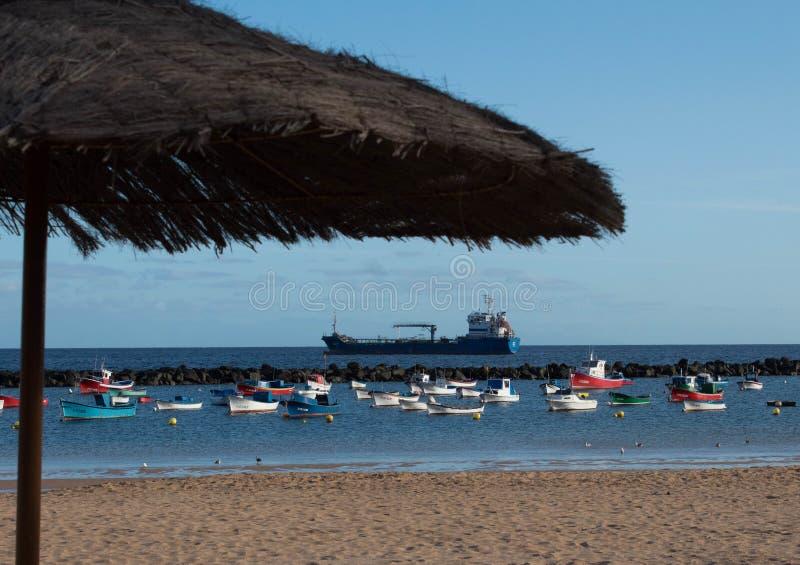 Het strandmening van Lasteresitas met boten en strandparaplu stock afbeelding