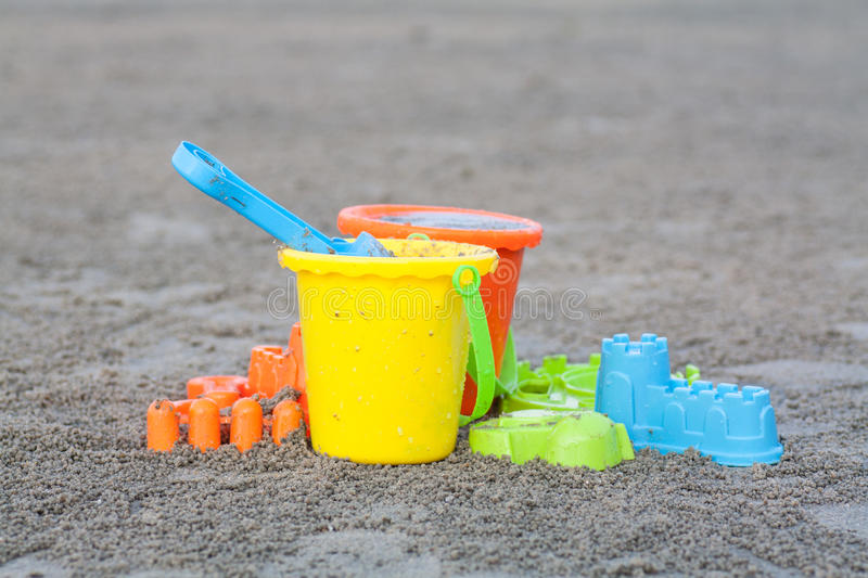 Het strandspeelgoed van kinderen - emmers, spade en schop op zand stock foto's