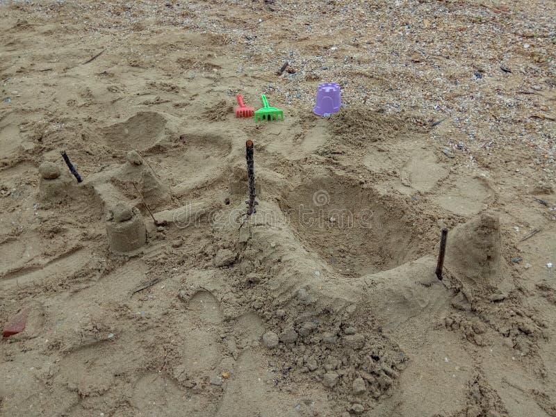 Het strandspeelgoed van kinderen - emmers, spade en schop op het zand stock afbeelding