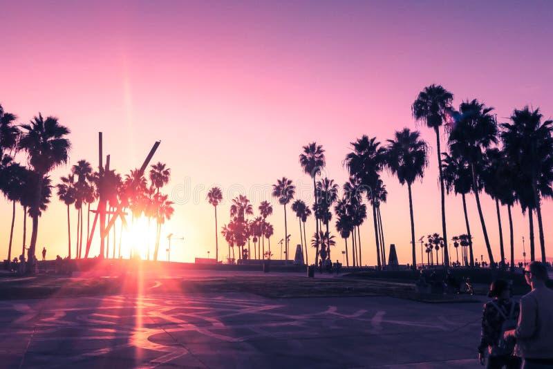 Het strandzonsondergang van Venetië in Los Angeles met een voetgang tijdens oranje zonsondergang Leeg strand stock foto's