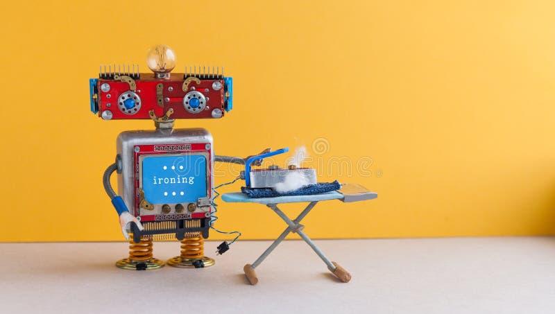 Het strijken van jeans met raad De helper van het robothuishoudelijk werk met ijzer, geel de ruimtebinnenland van de muur grijs v royalty-vrije stock afbeeldingen