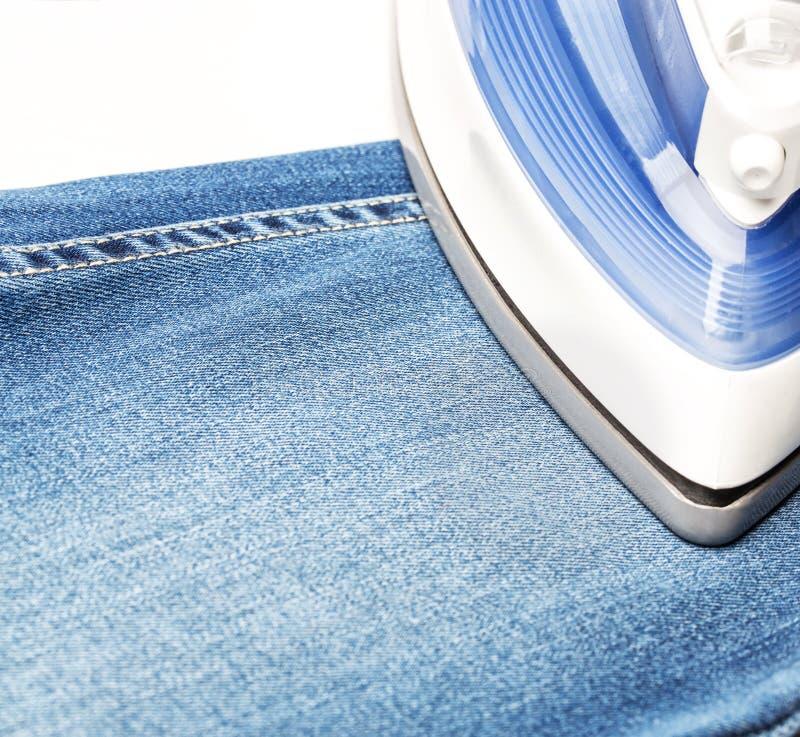 Het strijken van jeans op een witte baclground stock afbeelding