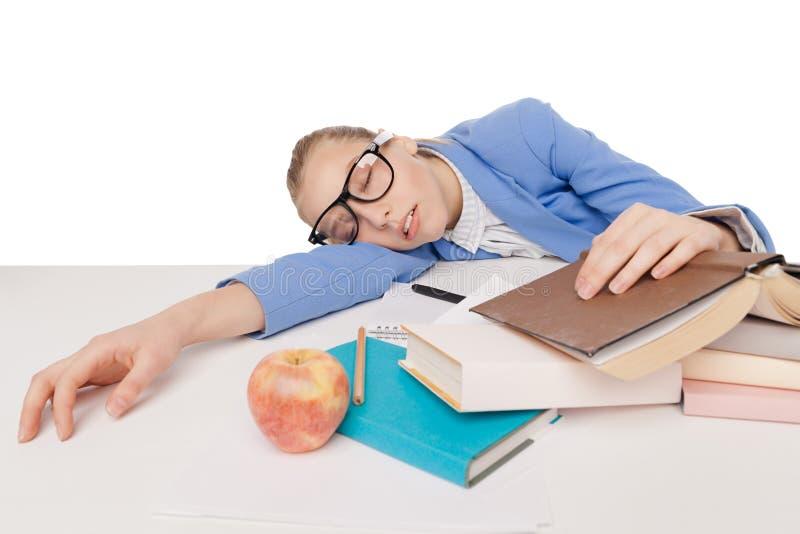 Het studentenmeisje in grote glazen zit en slaap stock foto