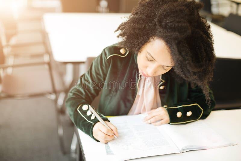 Het studentenmeisje schrijft een lezing bij de universiteit stock afbeeldingen
