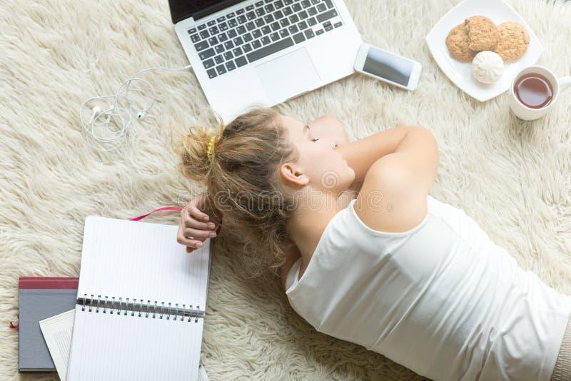 Het studentenmeisje viel in slaap na thuis het bestuderen stock foto