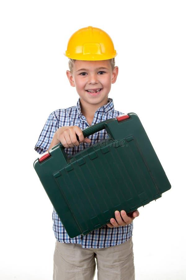 Het studiobeeld van een jonge gelukkige toekomstige bouwer in een mooi blauw checkred overhemd en gele helm, houdend toolbox stock afbeelding