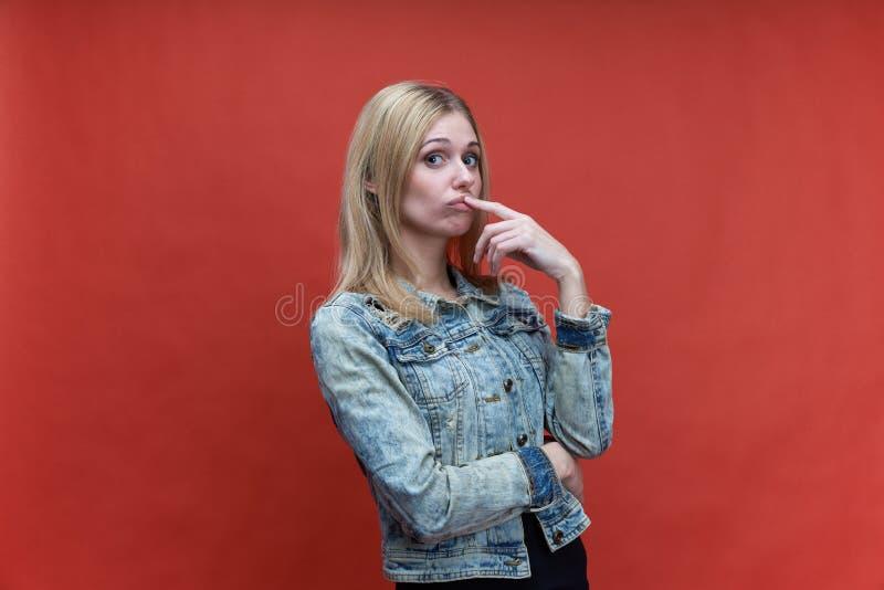 Het studioportret op rode achtergrondmeisjestiener met lang haar en een starende blik leidde bij de camera royalty-vrije stock afbeelding
