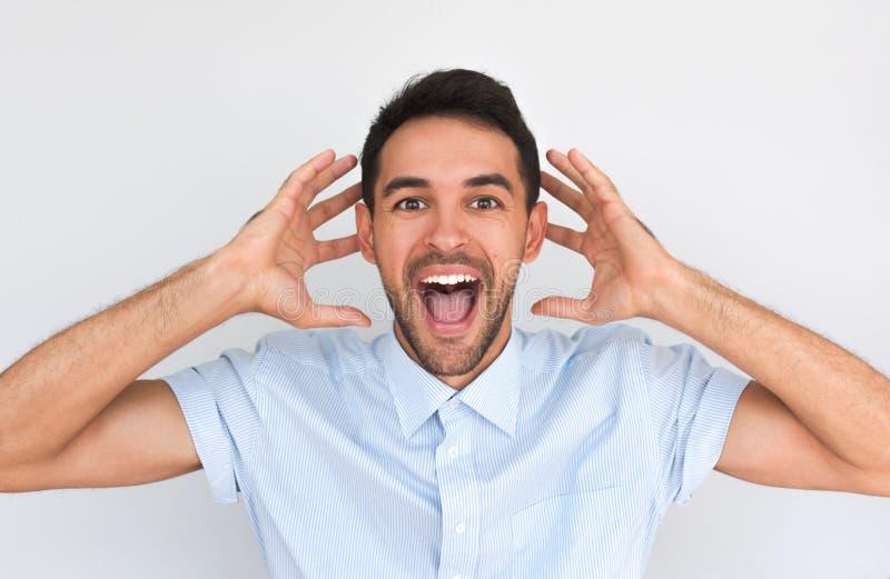 Het studioportret van de knappe gelukkige mens bereikt doelstellingen, dragend blauw overhemd makend verrast gebaar tegen studiom royalty-vrije stock afbeeldingen