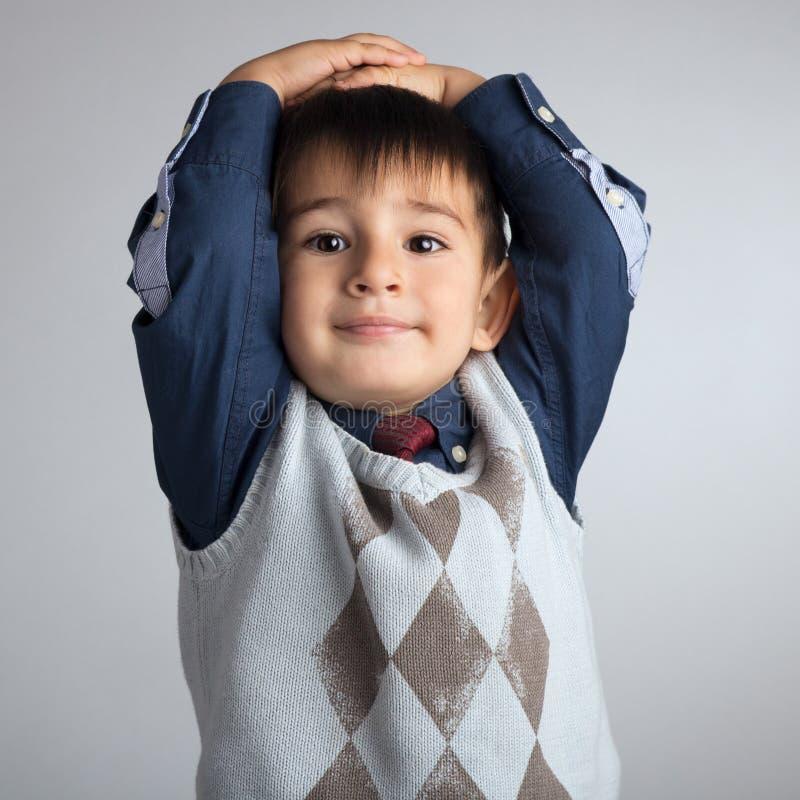 Het studioportret van een leuke kleine jongen, een kind wierp zijn handen achter zijn hoofd stock afbeeldingen