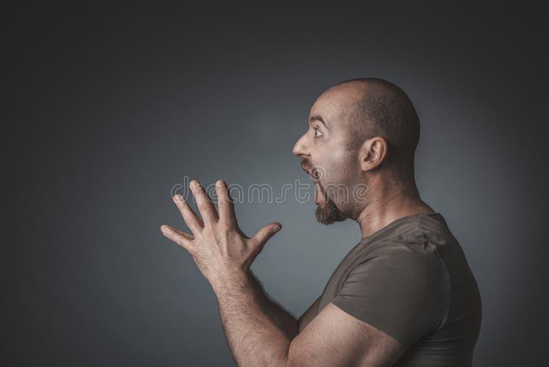 Het studioportret van een mens met verraste uitdrukking clasped handen royalty-vrije stock fotografie