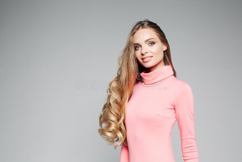 Het studioportret van een mooie bedrijfsvrouw blond met blauwe ogen met lang haar, draagt een elegante roze kleding en houdt royalty-vrije stock afbeeldingen