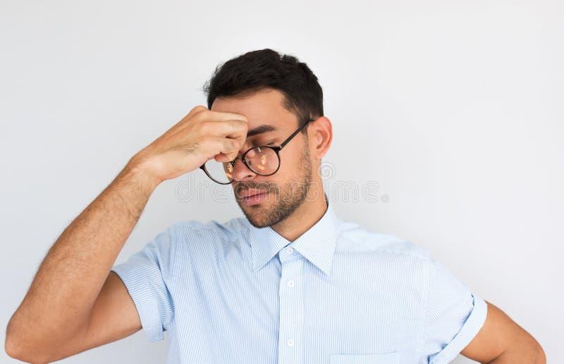 Het studioportret van mannetje draagt bril heeft hoofdpijn masserend neusbrug om spanning vrij te geven na het lange geïsoleerd w royalty-vrije stock foto's