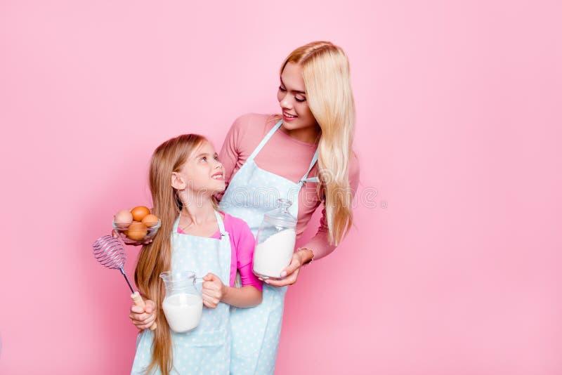 Het studioportret van moeder en dochter, die noodzakelijke ingrediënten voor cake hebben, die aan elkaar kijken, klaar voor kok,  stock fotografie