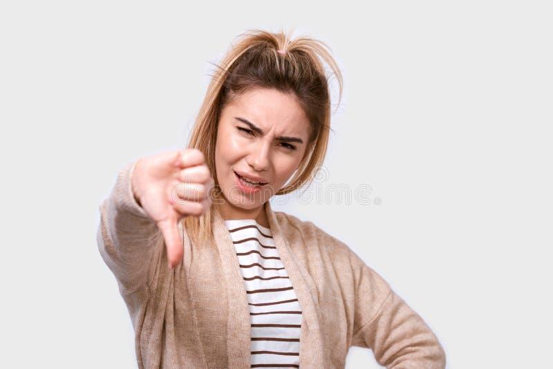 Het studioportret van het ongelukkige vrouw geven beduimelt onderaan gebaar kijkend met negatieve uitdrukking en afkeuring stock foto