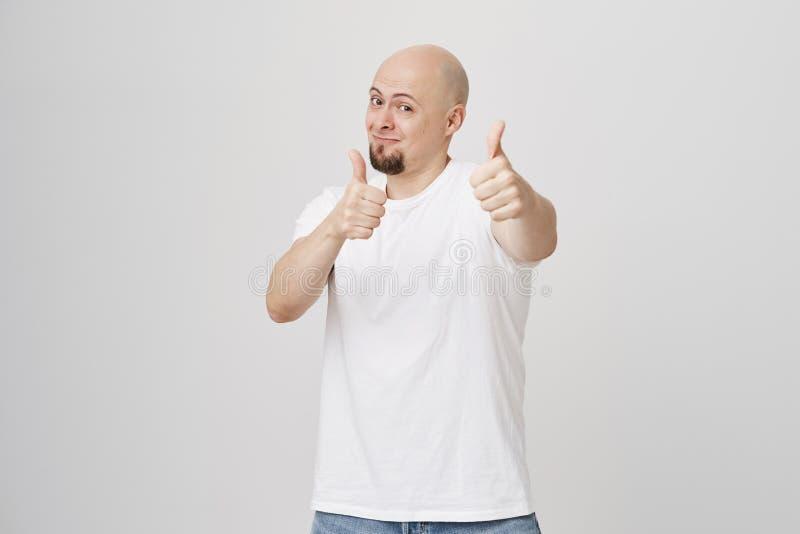 Het studioportret van positief wekte kaal gebaard duimen tonen bij camera en mannetje op die, status cheerfully glimlachen stock fotografie