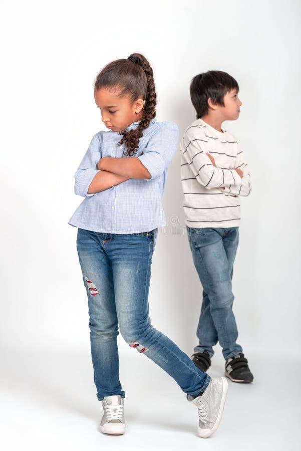 Het studioschot van aantrekkelijke jonge meisje en jongen met wapens kruiste beledigd elkaar r stock fotografie