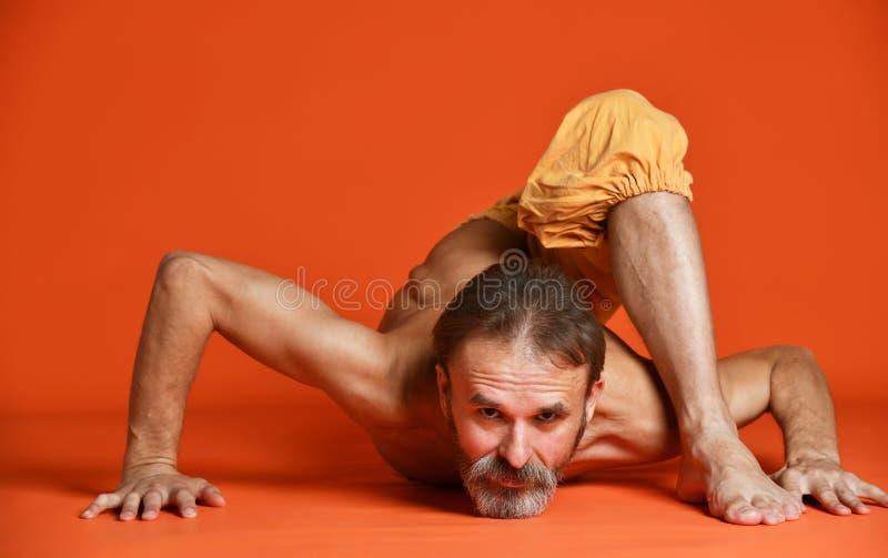 Het studioschot van de hogere gebaarde mens die yoga doen stelt en zijn shirtless benen uitrekken royalty-vrije stock foto's