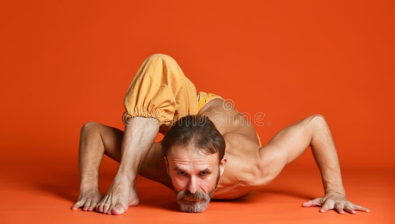 Het studioschot van de hogere gebaarde mens die yoga doen stelt en zijn shirtless benen uitrekken stock foto