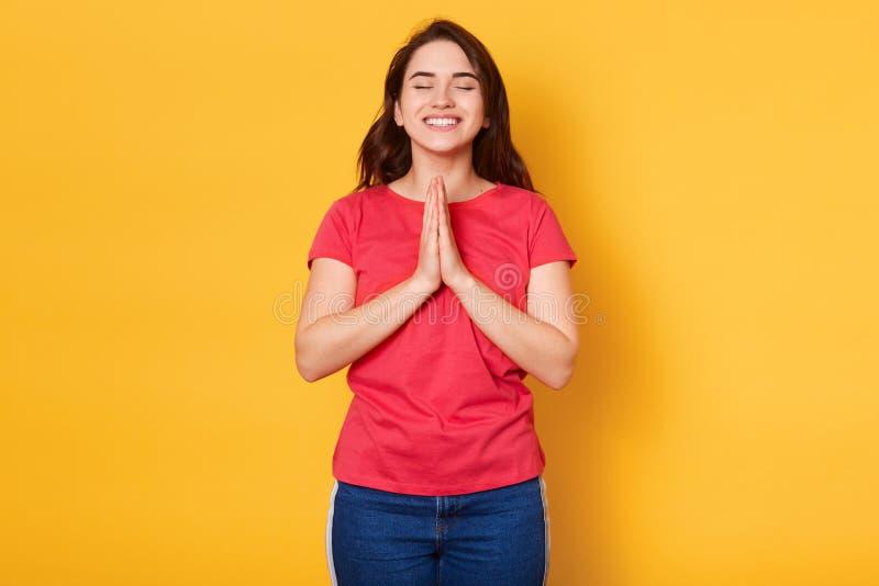 Het studioschot van donkerbruine vrouw bidt voor iets, die goed geluk wensen, heeft geloof voor beter, stellend met gesloten ogen stock afbeeldingen