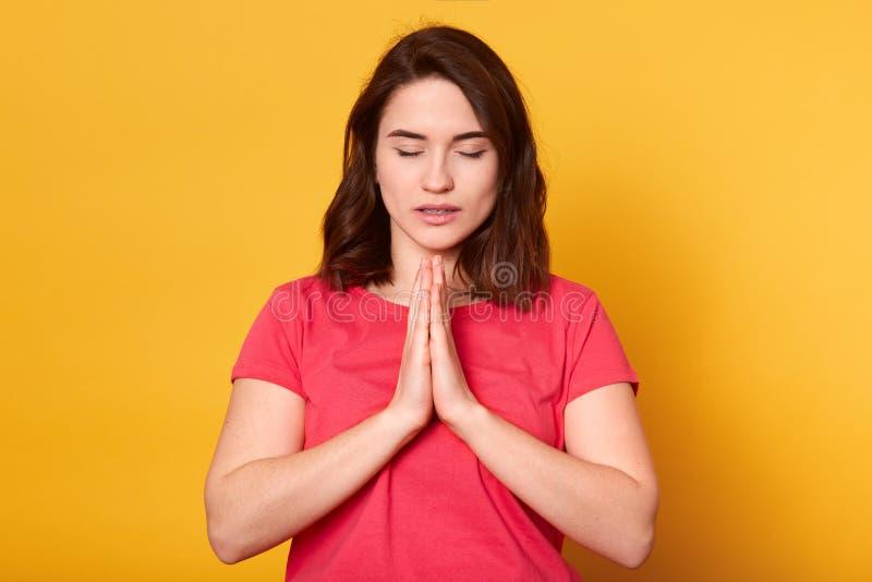Het studioschot van Kaukasisch wijfje bidt voor wellness van haar familie, houdt palmen samengeperst, stelt in het bidden van geb stock foto's
