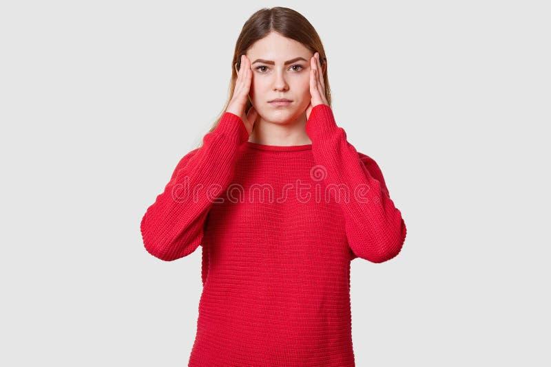 Het studioschot van ontstemd wijfje lijdt aan hoofdpijn, gekleed in rode sweater, houdt handen op tempels, heeft verstoord gezich stock afbeelding