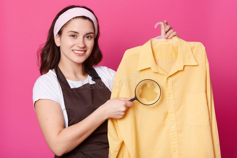 Het studioschot van prettige kijkende huisvrouw met prettige blik, draagt witte haarband, toevallige t-shirt, en de bruine schort stock afbeeldingen