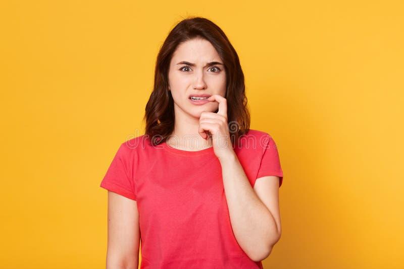 Het studioschot van vrouwelijk kereltje die volledig van vrees, houdt voorvinger dichtbij lippen, die diep in gedachten, die bang stock afbeelding