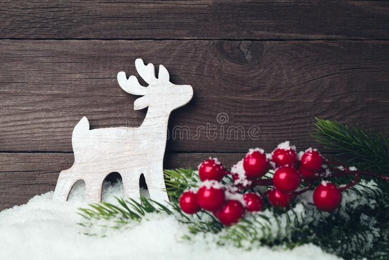Het stuk speelgoed en de boom van Kerstmisherten op sneeuw over houten achtergrond stock foto