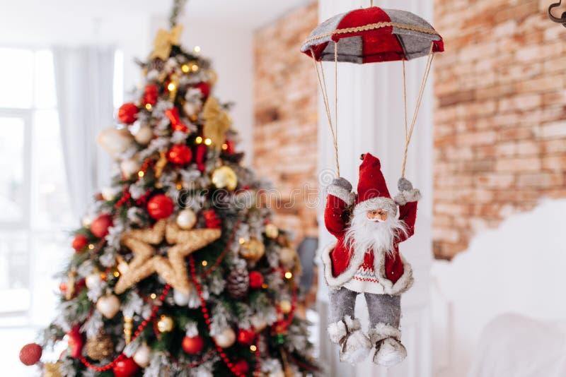Het stuk speelgoed van de Kerstman op valscherm brengt giften bij rode Kerstboom bokeh achtergrond De grote Copyspace-banner van  royalty-vrije stock fotografie
