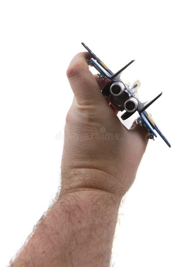 het stuk speelgoed van de luchtvechter in menselijke hand stock fotografie