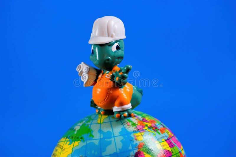 Het stuk speelgoed van kinderen cijfer - architect-bouwer met tekeningen op de bol van de Aarde Het stuk speelgoed is een vermind royalty-vrije stock foto's