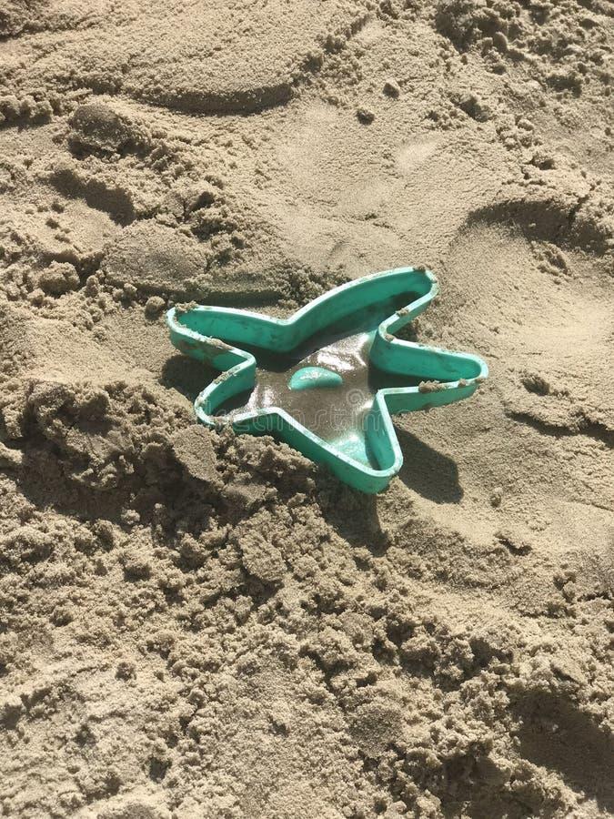 Het stuk speelgoed van het sterzand bij het strand stock afbeeldingen