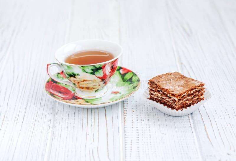Het stuk van chocoladecake en een kop thee op een witte lijst T royalty-vrije stock afbeelding