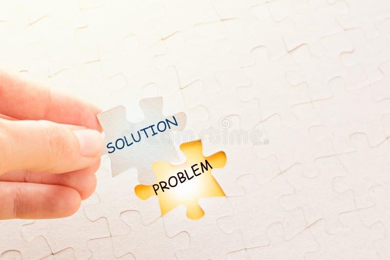Het stuk van de handholding van raadsel met woord oplossing en het zetten van het op plaats met probleem stock fotografie