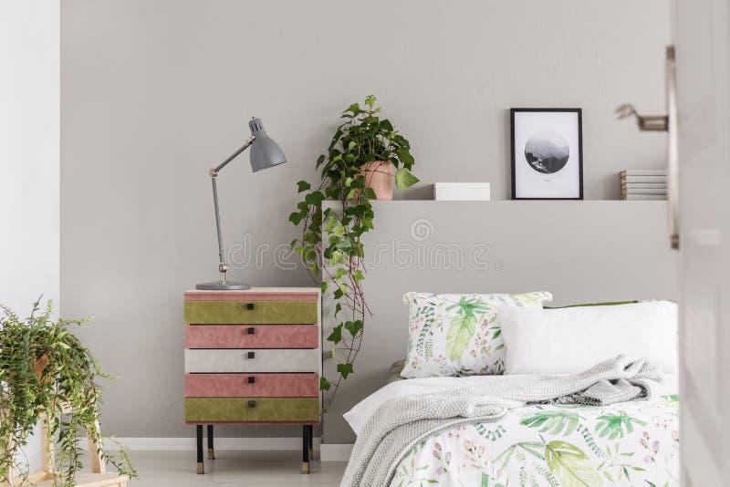 Het suède behandelde roze en olijf groene nightstand met grijze lamp in modieuze slaapkamer met bloemenbladen en groene installat royalty-vrije stock foto's