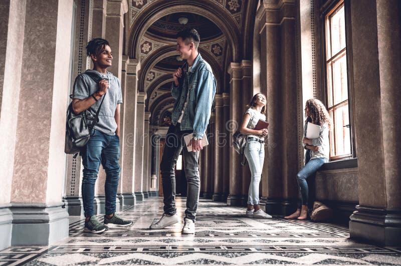 Het succes en de kennis helpen ons op het examen Gelukkige jonge studenten die zich bij de het universitaire zaal en babbelen bev royalty-vrije stock foto