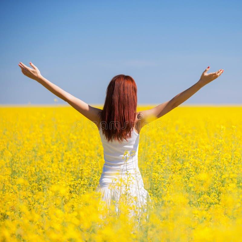 Het succesconcept van de mensenvrijheid Gelukkige vrouw op het gebied met bloemen bij zonnige dag in het platteland De achtergron stock foto