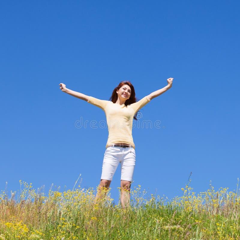 Het succesconcept van de mensenvrijheid Gelukkige vrouwendromen om op winden te vliegen Landschap van gras en bloem de zomergebie stock afbeeldingen