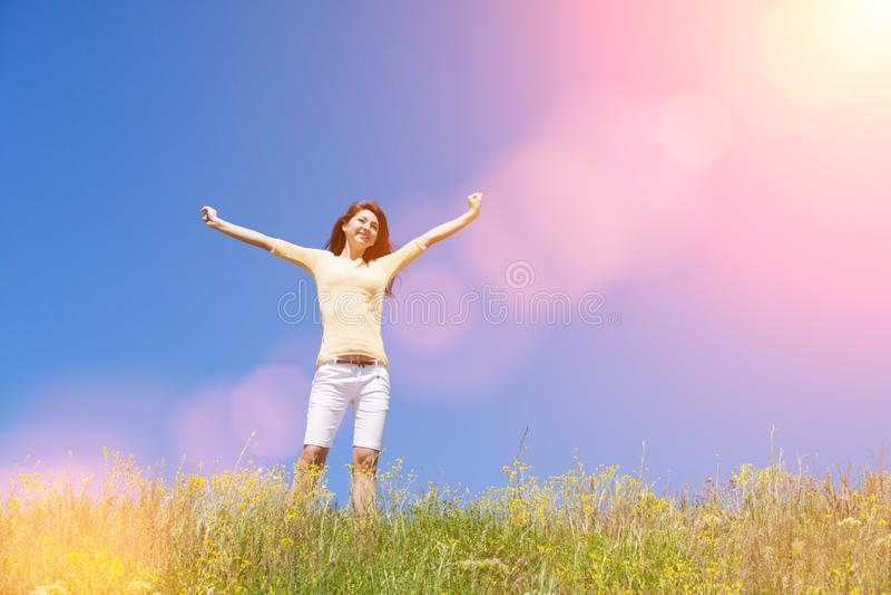 Het succesconcept van de mensenvrijheid Gelukkige vrouwendromen om op winden te vliegen Landschap van gras en bloem de zomergebie stock fotografie