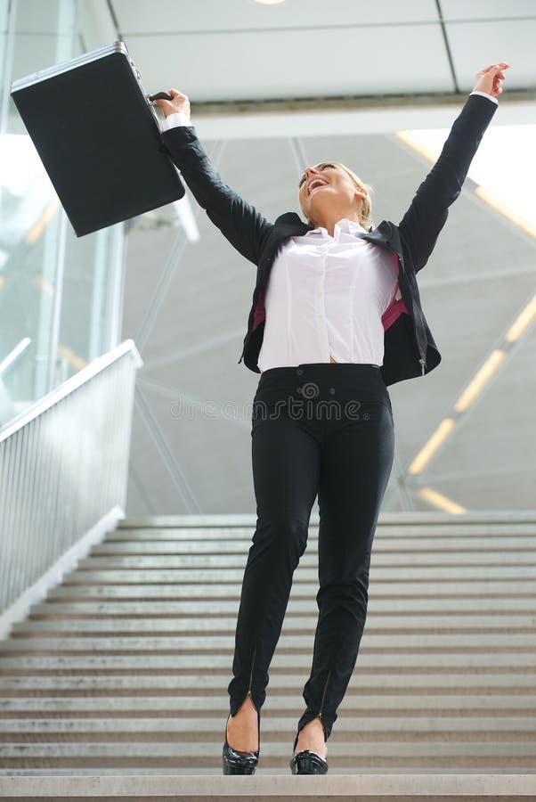 Het succesvolle bedrijfsvrouw vieren met opgeheven wapens stock afbeelding
